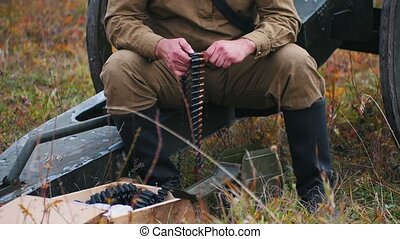 A man soldier prepares the ammunition for the charge in the machine gun - put the patrons in places. Mid shot