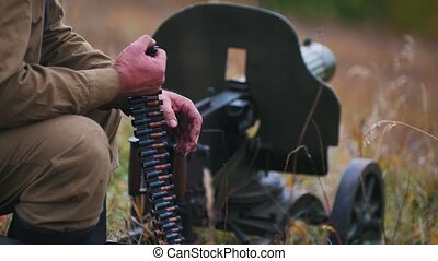 A man soldier prepares the ammunition for the charge in the machine gun - put the patrons in their places. Mid shot