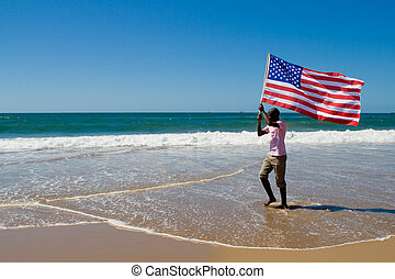 a man standing in the shallow waters of the ocean holding the USA flag