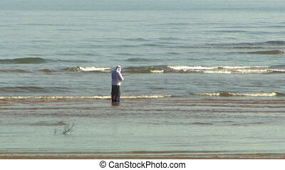 A man standing in the waves offshore, fishing - Wide shot of...