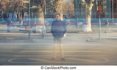 A man stands at a pedestrian crossing around a blurry people and blurry cars. Time Lapse video