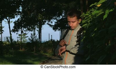 A man stands in a park with smart watch in his hands at sunrise. It responds to posts on the social network