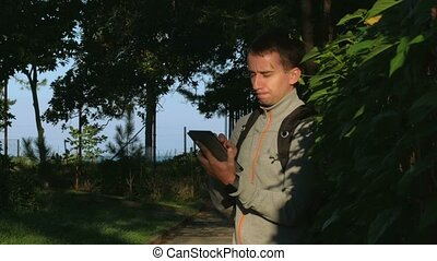 A man stands in a park with tablet computer in his hands at sunrise. It responds to posts on the social network