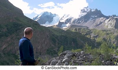 A man stands in front of the mountain peaks and points to them with his hand.