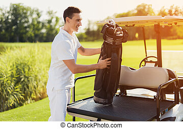 A man stands in white clothes and pulls out a bag for golf clubs from the trunk of a golf court
