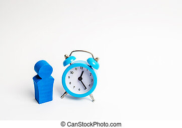 A man stands near a blue alarm clock and waits for someone. The concept of waiting for a meeting, a date. Late and punctual. The cost of hourly work of a specialist, business planning.
