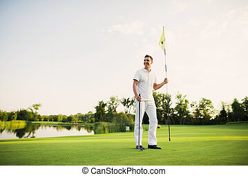 A man stands on a golf course, holds a golf club and flags for the hole