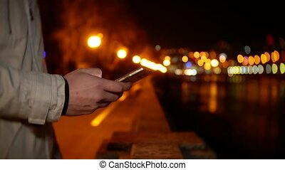 A man stands on the waterfront and uses the phone at night against a background of night lights. 4k, background blur