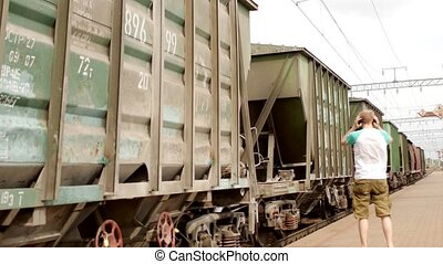 A man stands very close to a freight train and listens to music in headphones, a security breach on the railway