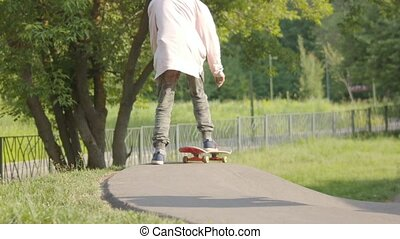 A man stepping on the skate and starts skateboarding on a...