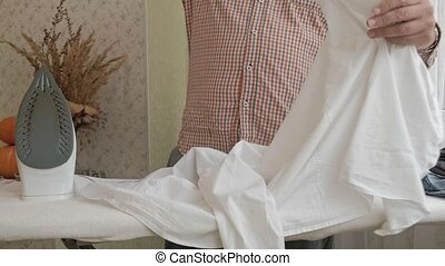 A man strokes his shirt on the ironing board in his house