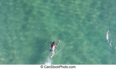A man swims in the sea. Aerial view from copter