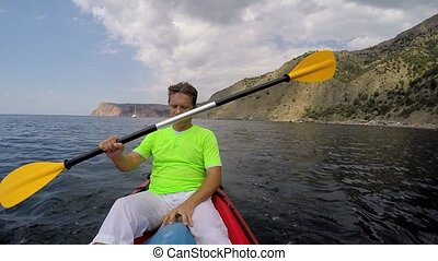 man swims into the sea in a kayak - a man swims into the sea...
