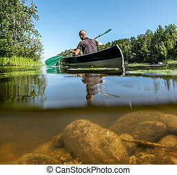 A man swims on a kayak on the lake in summer  day