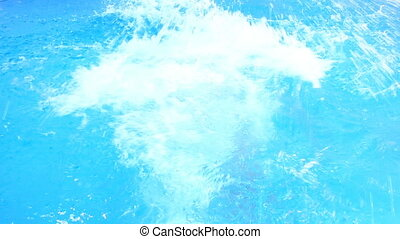A man swims under the water in a pool with blue water. view from above.