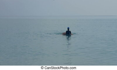 A man swims under the water with a diving mask and shoots video on the phone, taking selfies.
