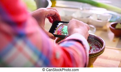 A man takes a picture of a dish on a smartphone