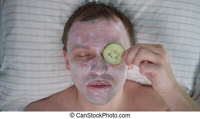 Man takes care of his face, lies with a cosmetic mask on his face, eats a slice of cucumber