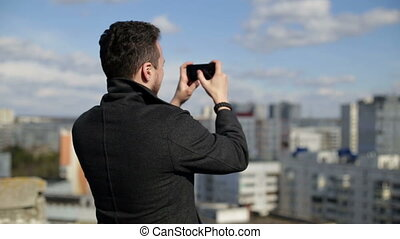 A man takes photos on the roof.
