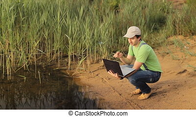 A man talking on a video on a laptop computer at the coast