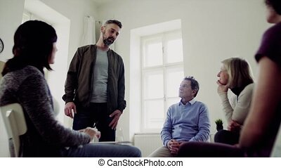 A man talking to other people during group therapy. - A...