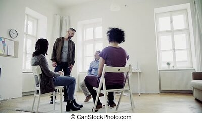 A man talking to other people during group therapy. Slow...