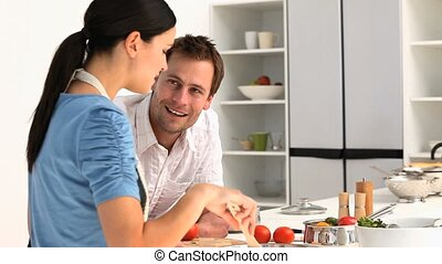 A man talking with his  girlfriend while she is cooking