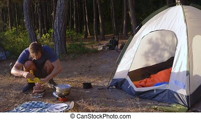 a man the campers, cooks food next to a tent on the edge of...