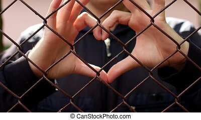 A man through the grid lattice shows a gesture of the heart,...