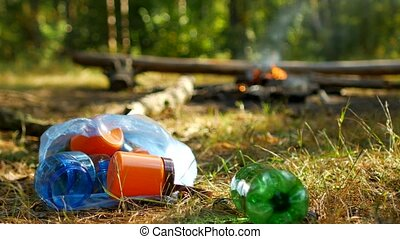 A man throws a plastic bottle in nature, a fire burns in the...