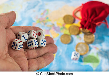 A man throws dice with red and blue markings on the world map. World order, map and money.