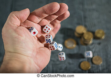 A man throws dice with red and blue markings on wooden table with coins.