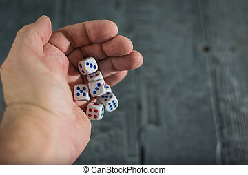 A man throws five dice on wood table.