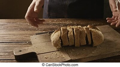 A man throws organic fresh sliced bread on a cutting wooden...
