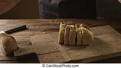 A man throws pieces of fresh white bread on a wooden board -...
