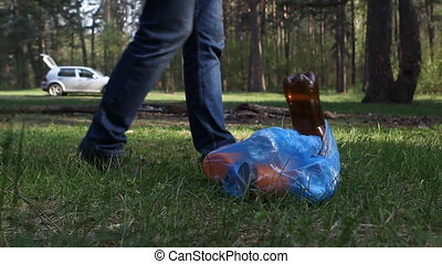 A man throws rubbish in the woods, close-up, trash