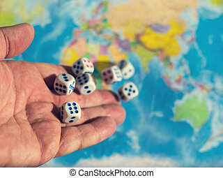 A man throws seven dice on the world map. The concept of ownership of the world. World order. d map and money