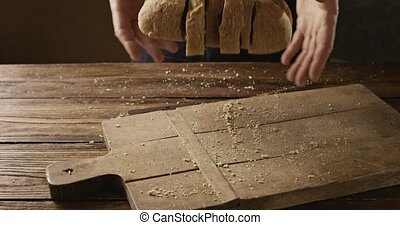 A man throws sliced fresh bread on an old wooden cutting...