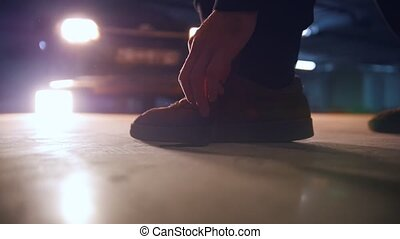 A man ties his shoelaces on sneakers in underground parking...
