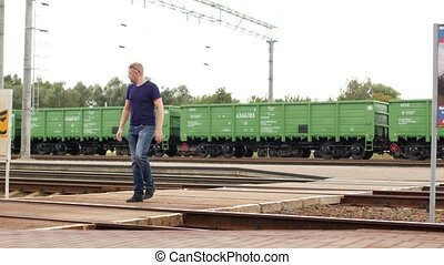 A man ties up his shoelaces on the railway tracks, a...