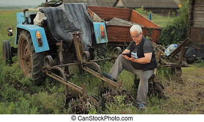 A man touch tablet near the tractor and move away. Agriculture surrounds
