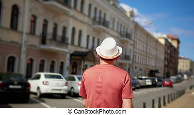 A man tourist in a white hat walks through the streets of the city, tracking cameras, back view