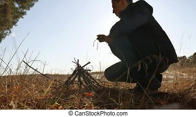 a man tourist is preparing bonfire a fire from the branches of trees. Boy Scout Kindle Campfire Camping lifestyle Outdoors Tourism Silhouette