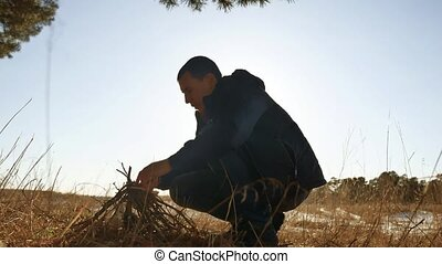 a man tourist is preparing bonfire a fire from the branches of trees. Boy Scout Kindle Campfire lifestyle Camping Outdoors Tourism Silhouette
