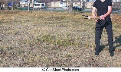 A man training his german shepherd dog - incite the dog on the grip bait and making the dog jump - a dog catching the bait. Mid shot