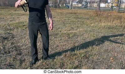 A man training his german shepherd dog - incite the dog on the grip bait and making the dog jump - a dog running in the circle and trying to catch the bait - outdoors tranining. Mid shot