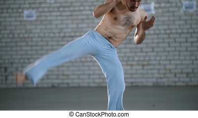 A man training his skills. Performing capoeira elements. Mid...