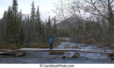 A man traveler crosses a mountain stream over a bridge....