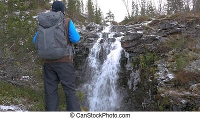 A man travels with a backpack along the mountain routes. He reached the beautiful waterfall, looked, and went on. Active and healthy life.