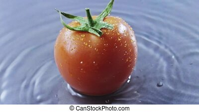 A man turns a tomato on a gray glass background covered with...